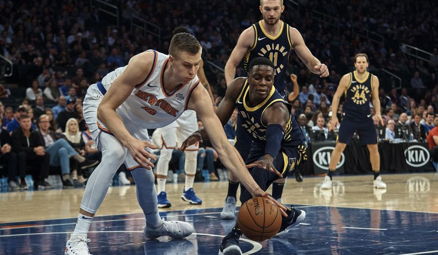 New York Knicks' Kristaps Porzingis, left, competes for the ball with Indiana Pacers' Darren Collison, centre, during the first half of a NBA basketball game at Madison Square Garden in New York, Sunday, Nov. 5, 2017. (AP Photo/Andres Kudacki)