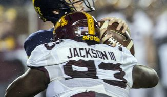 Michigan quarterback Brandon Peters (18) takes a hit by Minnesota defensive lineman Merrick Jackson (93) in the third quarter of an NCAA college football game in Ann Arbor, Mich., Saturday, Nov. 4, 2017. Michigan won 33-10. (AP Photo/Tony Ding)