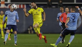 Columbus Crew's Justin Meram (9) is defended by New York City FC's Ben Sweat (2) during the first half of an MLS Eastern Conference semifinal soccer match Sunday, Nov. 5, 2017, in New York. (AP Photo/Mark Lennihan)