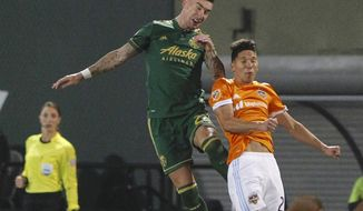 Portland Timbers' Liam Ridgewell (24) and a Houston Dynamo player try to win the ball in the second leg of their MLS Cup playoffs matchup of the Western Conference soccer semifinals in Portland, Ore., Sunday, Nov. 5, 2017. (Sean Meagher/The Oregonian via AP)