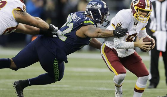 Washington Redskins quarterback Kirk Cousins, right, scrambles away from a tackle attempt by Seattle Seahawks defensive end Michael Bennett, left, in the second half of an NFL football game, Sunday, Nov. 5, 2017, in Seattle. (AP Photo/Stephen Brashear) ** FILE **