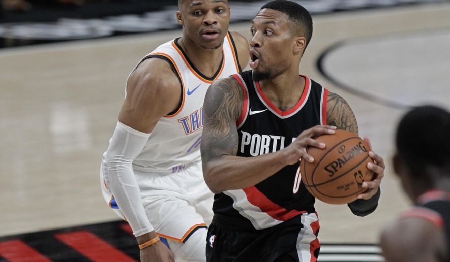Portland Trail Blazers guard Damian Lillard, right, looks to pass as Oklahoma City Thunder guard Russell Westbrook defends during the first half of an NBA basketball game in Portland, Ore., Sunday, Nov. 5, 2017. (AP Photo/Steve Dipaola)