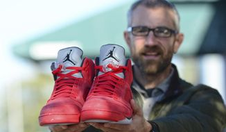 In this Thursday, Oct. 26, 2017 photo, The Rev. Joe DeScala of Mended, a non-denominational Christian church, holds up a pair of limited-edition Air Jordan athletic shoes in Port Angeles, Wash. DeScala and other community members purchased the shoes to replace those stolen from a 16-year-old Canadian tourist on Oct. 6. (Jesse Major/The Peninsula Daily News via AP)