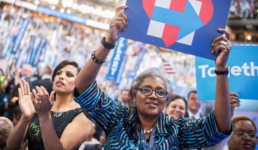 "What once was: Donna Brazile brandishes a Hillary Clinton campaign sign at the 2016 Democratic National Convention, 16 months before the publication of her new book ""Hacked."" It comes out Tuesday. (Associated Press)"