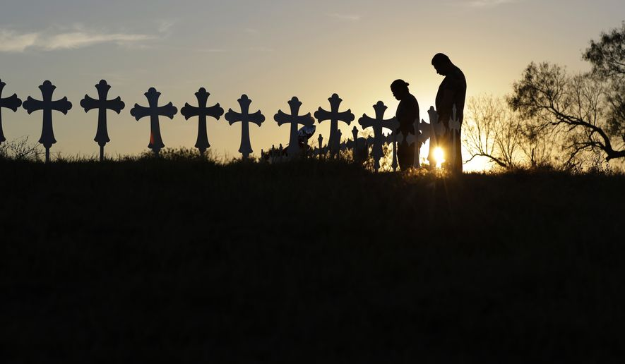 Kenneth and Irene Hernandez pay their respects as they visit a makeshift memorial with crosses placed near the scene of a shooting at the First Baptist Church of Sutherland Springs, Monday, Nov. 6, 2017, in Sutherland Springs, Texas. A man opened fire inside the church in the small South Texas community on Sunday, killing and wounding many. (AP Photo/Eric Gay)