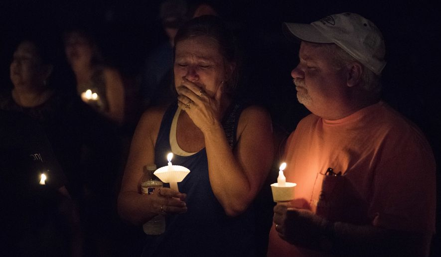 Mourners participate in a candlelight vigil for the victims of a fatal shooting at the First Baptist Church of Sutherland Springs, Sunday, Nov. 5, 2017, in Sutherland Springs, Texas. A man dressed in black tactical-style gear and armed with an assault rifle opened fire inside the church in the small South Texas community on Sunday, killing and wounding many. The dead ranged in age from 5 to 72 years old. (AP Photo/Darren Abate)