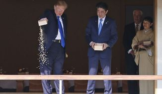 U.S. President Donald Trump pours out the remaining  fish food from a container as he feeds carp at a koi pond with Japan's Prime Minister Shinzo Abe, third from right, before their working lunch at Akasaka Palace in Tokyo, Japan Monday, Nov. 6, 2017. (Toru Hanai/Pool Photo via AP)