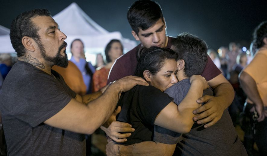 Jennifer Palacios, center, the biological mother of 14-year-old Annabelle Pomeroy who died in a mass shooting in Sutherland Springs, Texas, is comforted by, from left to right, her boyfriend Fritz Rymers, her son Timothy Rodriguez and her mother Diana Palacios, at a memorial service in Sutherland Springs, Monday, Nov. 6, 2017. (Jay Janner/Austin American-Statesman via AP)
