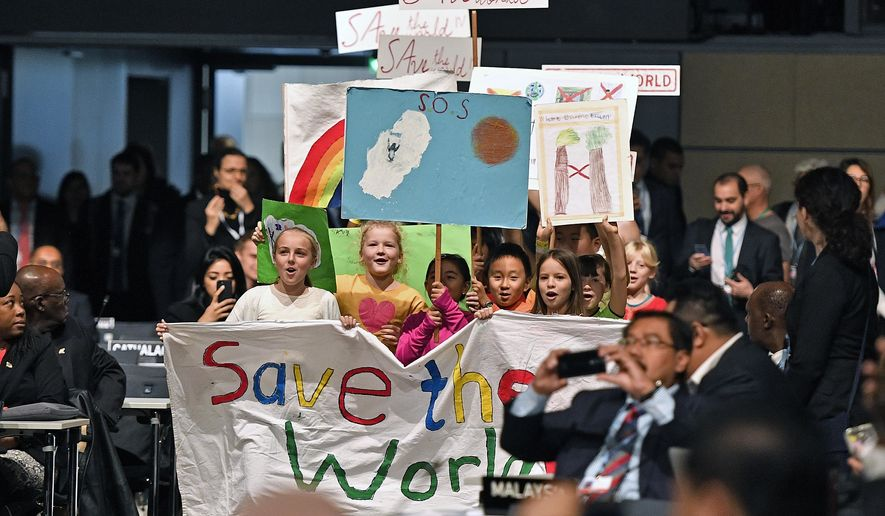 """Children with banners reading """"save the world"""" march between the delegates during the opening of the COP 23 Fiji UN Climate Change Conference in Bonn, Germany, Monday, Nov. 6, 2017. (AP Photo/Martin Meissner)"""