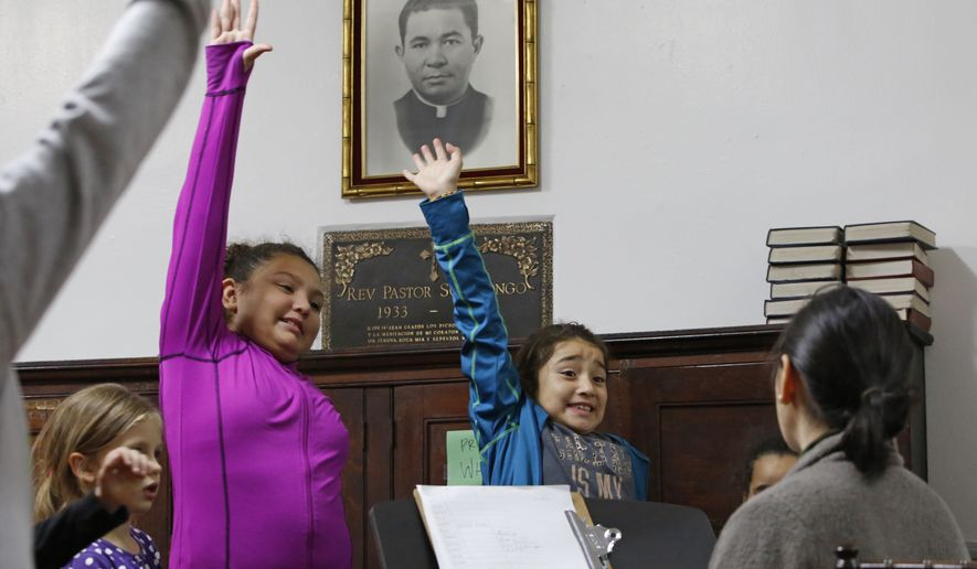 In this Oct. 26, 2017, photo, Dulce Carvajal, 10, second from left, and her sister Daniela, 8, raise their hands during voice lessons at the Holyrood Episcopal Church in the Bronx borough of New York. Since August, the girls and their brother have been living inside the church with their mother, a Guatemalan immigrant living illegally in the United States. At least two dozen immigrants have sought sanctuary at U.S. churches since the Immigration and Customs Enforcement agency stepped up arrests by 40 percent under President Donald Trump. (AP Photo/Kathy Willens)