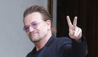 In this Monday, July 24, 2017, file photo, U2 singer Bono makes a peace sign as he arrives for a meeting at the Elysee Palace, in Paris, France. (AP Photo/Michel Euler, file)