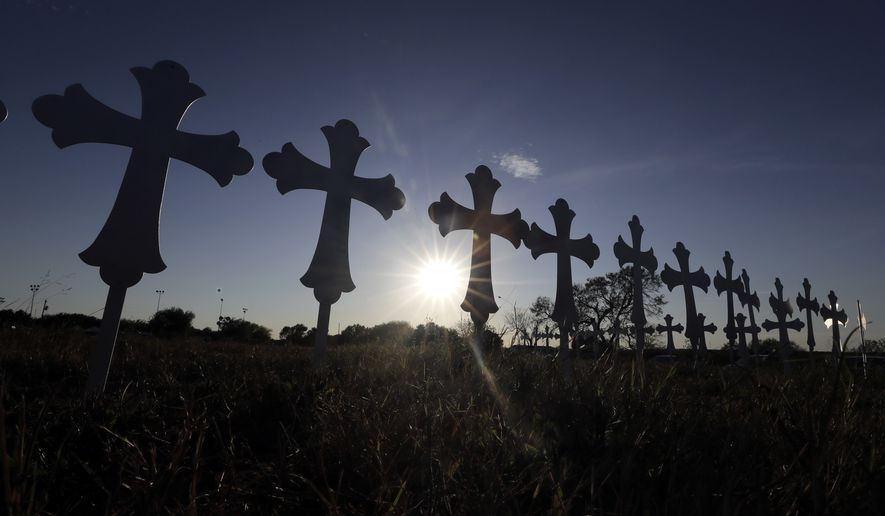 The sun sets behind 26 crosses placed in a field before a vigil for the victims of the First Baptist Church shooting Monday, Nov. 6, 2017, in Sutherland Springs, Texas. Texas officials confirmed Devin Patrick Kelley as the shooter who killed at least 26 people and wounded about 20 others at the church. (AP Photo/David J. Phillip)