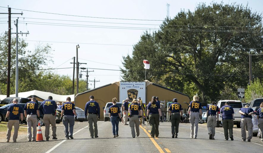 FBI agents search for evidence on a road near First Baptist Church in Sutherland Springs, Texas on Monday, Nov. 6, 2017. A man opened fire inside the church in the small South Texas community on Sunday, killing more than two dozen and wounding others. (Jay Janner/Austin American-Statesman via AP)