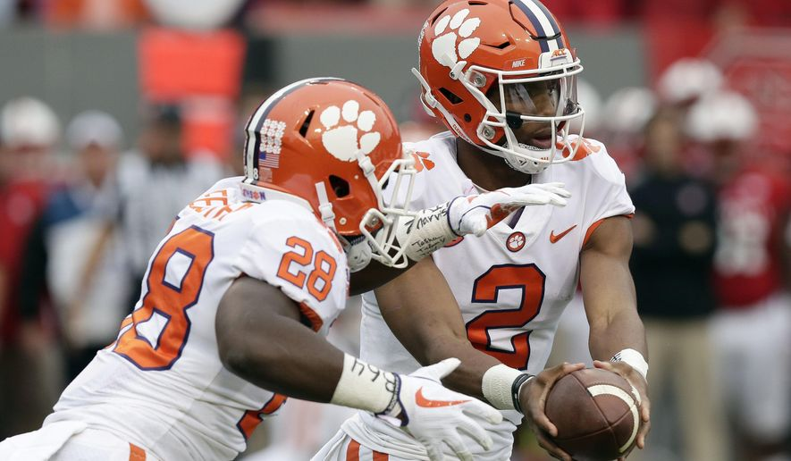 Clemson quarterback Kelly Bryant (2) hands off to Tavien Feaster (28) during the first half of an NCAA college football game against North Carolina State in Raleigh, N.C., Saturday, Nov. 4, 2017. (AP Photo/Gerry Broome)