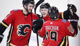 Calgary Flames' Matthew Tkachuk, right, celebrates his game-winning shootout goal with teammates Matt Stajan, centre, and T.J. Brodie during overtime of an NHL hockey against the New Jersey Devils in Calgary, Alberta, Sunday, Nov. 5, 2017. (Jeff McIntosh/The Canadian Press via AP)