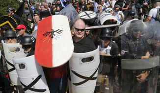 FILE - In this Aug. 12, 2017, file photo, white nationalist demonstrators use shields as they guard the entrance to Lee Park in Charlottesville, Va. Anxious to avoid the mayhem that has erupted at gatherings such as in Charlottesville over the past year, law enforcement agencies are comparing notes and honing their tactics. (AP Photo/Steve Helber, File)