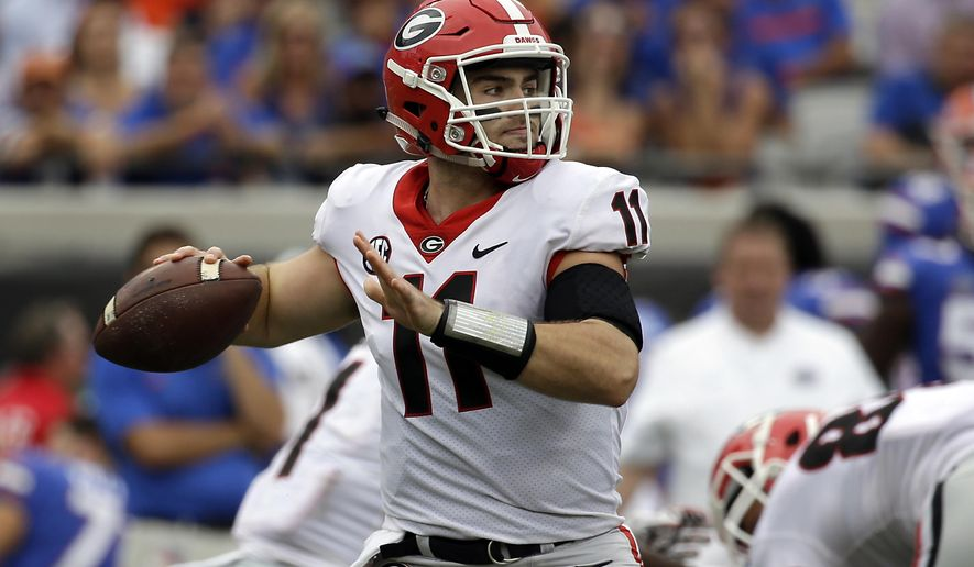 FILE - In this Saturday, Oct. 28, 2017 file photo, Georgia quarterback Jake Fromm throws a pass against Florida in the first half of an NCAA college football game in Jacksonville, Fla. Jake Fromm hardly looks like someone who was playing high school football a year ago. He stepped right in when Georgia's starter was injured in the very first game. The No. 2 Bulldogs are trying to become only the second team to win a national title with a true freshman quarterback. (AP Photo/John Raoux, File)