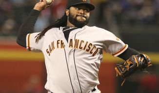 In this Sept. 25, 2017, photo, San Francisco Giants' Johnny Cueto delivers a pitch to the Arizona Diamondbacks during the first inning of a baseball game in Phoenix. Giants won 9-2 over the Diamondbacks. Right-hander Cueto is staying with the San Francisco Giants. He had the option to opt out of his contract that runs through 2021. The team said Sunday, Nov. 5, the pitcher had decided to remain with the Giants. (AP Photo/Darryl Webb)
