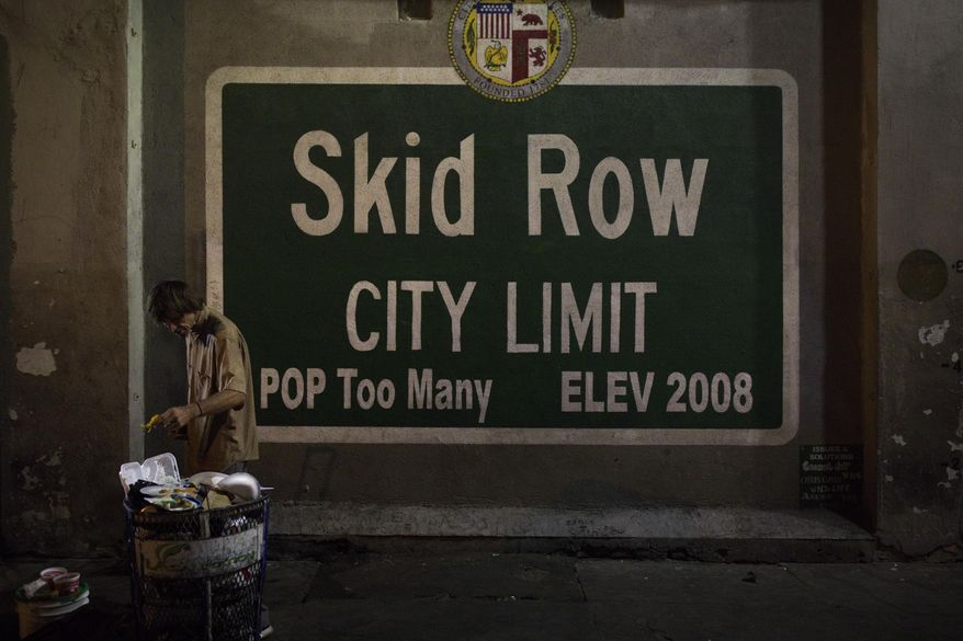 A homeless man takes food from a trash can in Los Angeles' Skid Row area, home to the nation's largest concentration of homeless people, Saturday, Oct. 28, 2017, in Los Angeles. (AP Photo/Jae C. Hong)