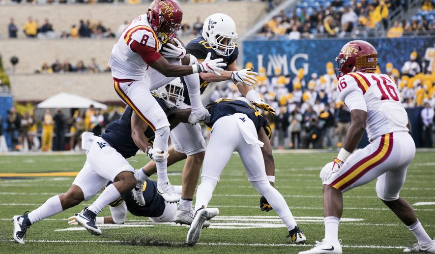 Iowa State wide receiver Deshaunte Jones (8) jumps over West Virginia defenders during the first half of an NCAA college football game in Morgantown, W. Va., Saturday, Nov. 4, 2017. (AP Photo/Walter Scriptunas II) I)