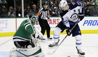 Dallas Stars' Ben Bishop (30) defends against pressure from Winnipeg Jets center Mark Scheifele (55) in the second period of an NHL hockey game, Monday, Nov. 6, 2017, in Dallas. (AP Photo/Tony Gutierrez)