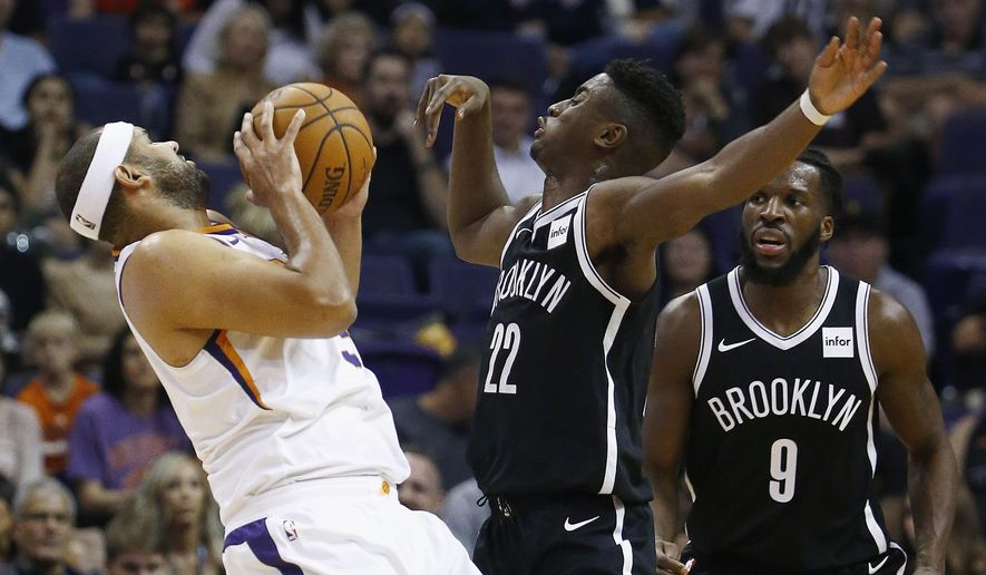 Brooklyn Nets guard Caris LeVert (22) collides with Phoenix Suns forward Jared Dudley, left, as Nets' DeMarre Carroll (9) looks on during the first half of an NBA basketball game Monday, Nov. 6, 2017, in Phoenix. (AP Photo/Ross D. Franklin)