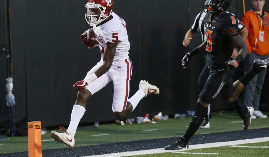 Oklahoma wide receiver Marquise Brown (5)t scores in front of Oklahoma State cornerback Rodarius Williams (8) in the second half of an NCAA college football game in Stillwater, Okla., Saturday, Nov. 4, 2017. Oklahoma won 62-52. (AP Photo/Sue Ogrocki)