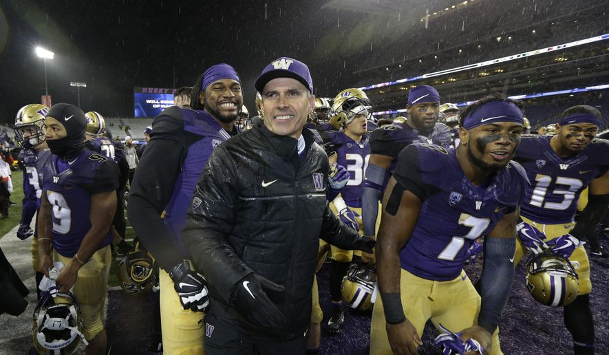 Washington head coach Chris Petersen, center, leads his team off the field after they beat Oregon 38-3 in an NCAA college football game, Saturday, Nov. 4, 2017, in Seattle. Washington won, 38-3. (AP Photo/Ted S. Warren)