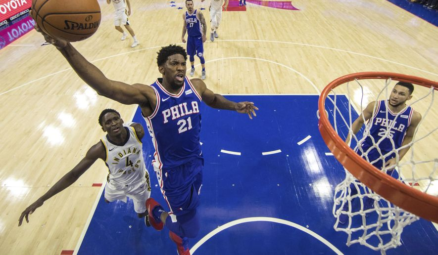 Philadelphia 76ers' Joel Embiid goes up for a shot with Indiana Pacers' Victor Oladipo, left, trailing during the first half of an NBA basketball game, Friday, Nov. 3, 2017, in Philadelphia. The 76ers won 121-110. (AP Photo/Chris Szagola)