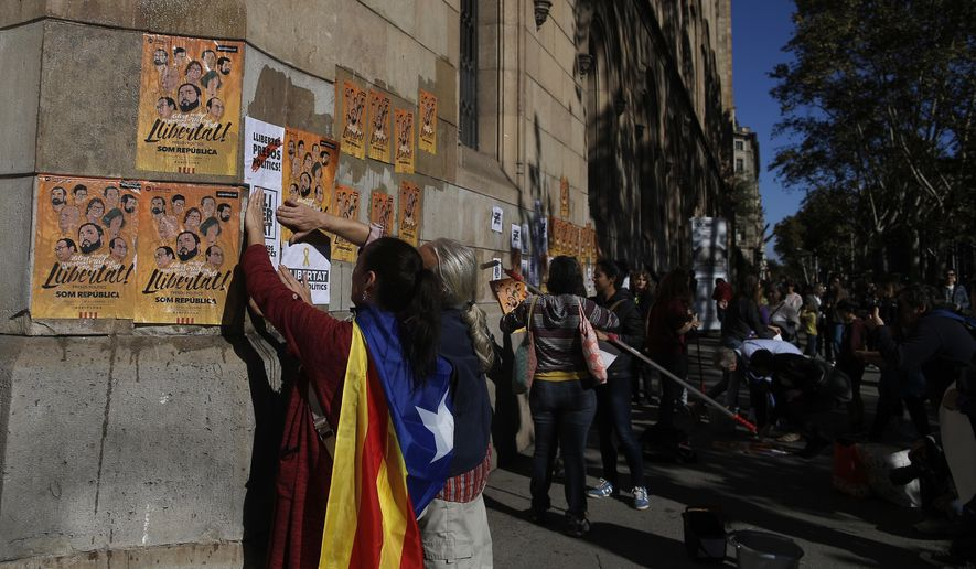 "A woman with an 'Estelada', the pro-independence Catalan flag draped over her shoulder, pastes banners on a wall that read in Catalan: ""Freedom for the Political Prisoners"" during a protest against the decision of a judge to jail ex-members of the Catalan government at the University square in Barcelona, Spain, Sunday, Nov. 5, 2017. A Spanish judge issued an international arrest warrant on Friday for former members of the Catalan Cabinet who were last seen in Brussels, including the ousted separatist leader Carles Puigdemont, who said he was prepared to run for his old job even while battling extradition in Belgium. (AP Photo/Manu Fernandez)"