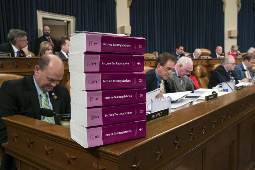 Volumes of tax regulations are stacked on the dais as the House Ways and Means Committee begins the markup process of the GOP's far-reaching tax overhaul, the first major revamp of the tax system in three decades, on Capitol Hill in Washington, Monday, Nov. 6, 2017. (AP Photo/J. Scott Applewhite)