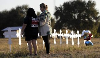 Laura Torres, right, and Sonia Yanez visit a line of crosses before a vigil for the victims of Sunday's First Baptist Church shooting, Monday, Nov. 6, 2017, in Sutherland Springs, Texas. A man opened fire inside the church in the small South Texas community on Sunday, killing more than 20 and wounding many. (AP Photo/David J. Phillip)