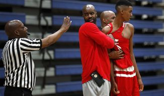 In this Oct. 8, 2017, photo, E.J. Bates holds his son Emoni back after an argument against a Howell High School player during a fall league basketball game in Saline, Mich. (AP Photo/Paul Sancya)
