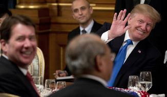 U.S. President Donald Trump, right, accompanied by U.S. Ambassador to Japan William F. Hagerty, left, waves to a guest during a state banquet at the Akasaka Palace, Monday, Nov. 6, 2017, in Tokyo. Trump is on a five-country trip through Asia traveling to Japan, South Korea, China, Vietnam and the Philippines. (AP Photo/Andrew Harnik)