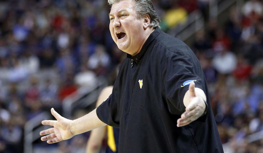 FILE - In this March 23, 2017, file photo, West Virginia head coach Bob Huggins yells from the sideline during the first half of an NCAA Tournament college basketball regional semifinal game against Gonzaga in San Jose, Calif. Huggins has agreed to a four-year contract extension the 2021-22 season. The 64-year-old Huggins will earn $3.75 million this season, including a base salary of $250,000. Under the agreement, starting with the in 2022-23 season, Huggins can assume a five-year appointment in public relations and development along with other duties within the athletic department, ending in June 2027. Or Huggins can choose to continue serving as head coach.  (AP Photo/Tony Avelar, File)
