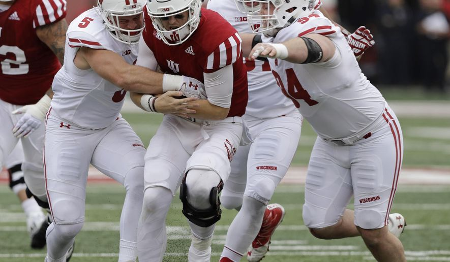 Indiana quarterback Richard Lagow (21) is tackled by Wisconsin's Garret Dooley (5) and Conor Sheehy (94) during the second half of an NCAA college football game, Nov. 4, 2017, in Bloomington, Ind. Wisconsin won 45-17. (AP Photo/Darron Cummings)