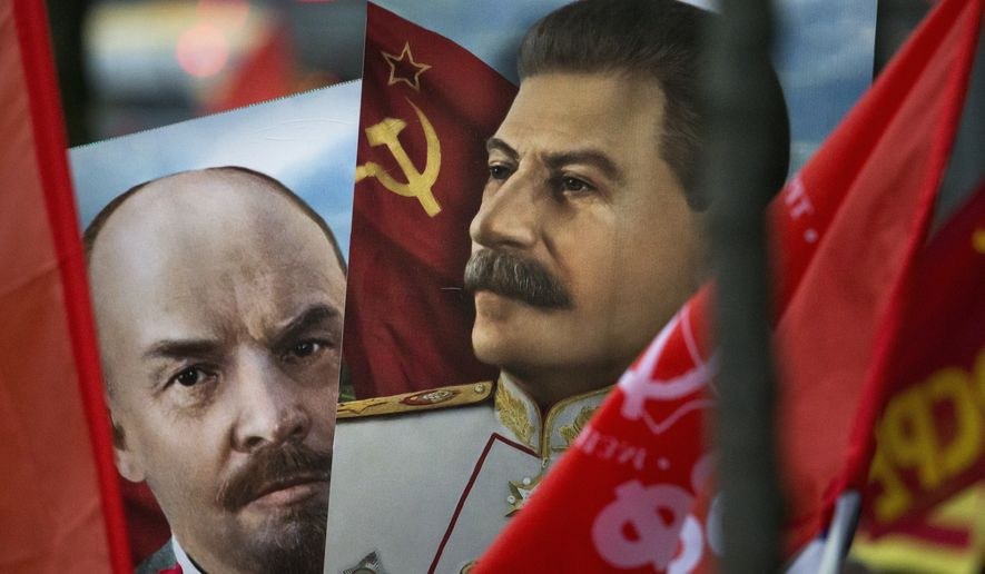 Communist party supporters carry portraits of Soviet founder Vladimir Lenin, left, and Soviet dictator Josef Stalin during a demonstration marking the 100th anniversary of the 1917 Bolshevik revolution in Moscow, Russia, Tuesday, Nov. 7, 2017. Thousands of Communist demonstrators marked the centennial of the 1917 Bolshevik revolution Tuesday by marching across downtown Moscow. (AP Photo/Alexander Zemlianichenko)