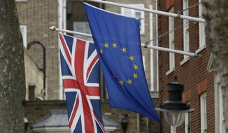 In this file photo dated Tuesday, March 14, 2017, a European flag flies along with a British Union flag, left, outside Europe House, the European Parliament's British offices, in London. (AP Photo/Matt Dunham, File)