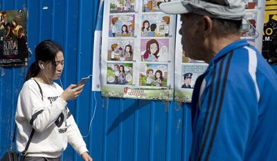 A woman walks past a poster warning against foreign spies displayed in an alleyway in Beijing, China, Wednesday, April 20, 2016. China is marking National Security Education Day with the poster warning young female government workers about dating handsome foreigners, who could turn out to have secret agendas. (AP Photo/Ng Han Guan)