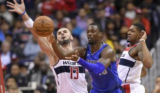 Dallas Mavericks forward Harrison Barnes, center, passes the ball against Washington Wizards center Marcin Gortat (13), of Poland, and guard Bradley Beal (3) during the second half of an NBA basketball game, Tuesday, Nov. 7, 2017, in Washington. The Mavericks won 113-99. (AP Photo/Nick Wass)
