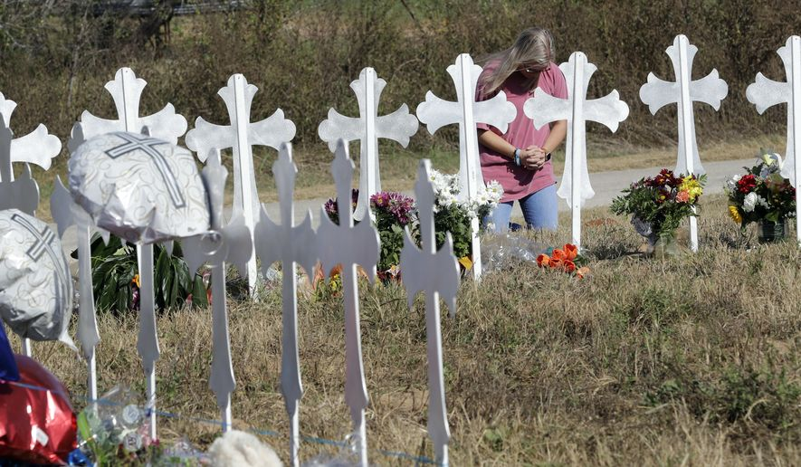A woman kneels in prayer at a makeshift memorial for the First Baptist Church shooting victims Tuesday, Nov. 7, 2017, in Sutherland Springs, Texas. A man opened fire inside the church in the small South Texas community on Sunday, killing more than two dozen and injuring others. (AP Photo/David J. Phillip)