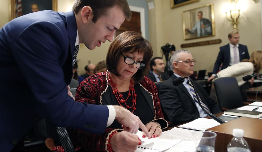An aide, left, assists Natalie Jaresko, executive director, and Noel Zamot, revitalization coordinator, both of the financial oversight and management board for Puerto Rico, before the start of a House Committee on Natural Resources hearing to examine challenges in Puerto Rico's recovery and the role of the financial oversight and management board, on Capitol Hill, Tuesday, Nov. 7, 2017 in Washington. (AP Photo/Alex Brandon)