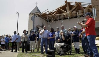 FILE - in this Aug. 31, 2017 file photo, Vice President Mike Pence, with his wife Karen, speaks to residents affected by Hurricane Harvey during a visit to the First Baptist Rockport Church in Rockport, Texas. The Federal Emergency Management Agency is rethinking a policy that routinely denies aid to religious institutions if the money will be used to rebuild sanctuaries damaged or destroyed in natural disasters. Several churches hit by recent hurricanes are challenging the policy in court. First Baptist's Senior Pastor Scott Jones said he doesn't fault others who seek FEMA aid, but his church won't be doing so. (AP Photo/Eric Gay, File)
