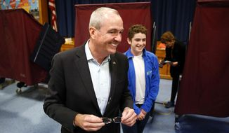 Democrat Phil Murphy exits the polling booth with his youngest son Sam, after voting at the Fairview School on Tuesday, Nov. 7, 2017 in Middletown, N.J.  Murphy is facing Republican Lt. Gov. Kim Guadagnoto to replace Gov. Chris Christie, the two-term, term-limited incumbent.   (Bob Karp/The Daily Record via AP)