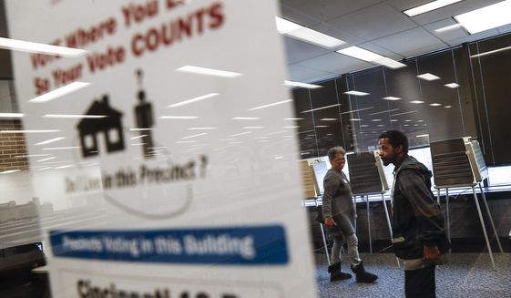 Polling workers mill about an empty voting location at the University of Cincinnati on Nov. 7, 2017. (Associated Press) **FILE**