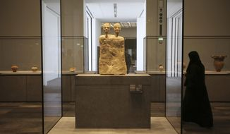 "In this Monday, Nov. 6, 2017, photo, an Emirati woman passes by ""Monumental Statue with two heads"" from Jordan about 6500 BCE, at the Louvre Abu Dhabi, United Arab Emirates. The Louvre Abu Dhabi is preparing its grand opening _ unveiling its treasures to the world after a decade-long wait and questions over laborers' rights. The museum, which opens on Saturday to the public, encompasses work from both the East and West. (AP Photo/Kamran Jebreili)"