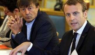 """FILE - In this Sept.5 2017 file photo, French President Emmanuel Macron, right, and Environment Minister Nicolas Hulot meet with NGOs to discuss climate and environment at the Elysee Palace in Paris. Macron is planning a climate summit next month to push his """"Make our Planet Great Again"""" agenda, and to unveil the winners of his fellowship competition for U.S. climate scientists frustrated by the Trump administration's attitude toward global warming. (Philippe Wojazer , Pool via AP, File)"""