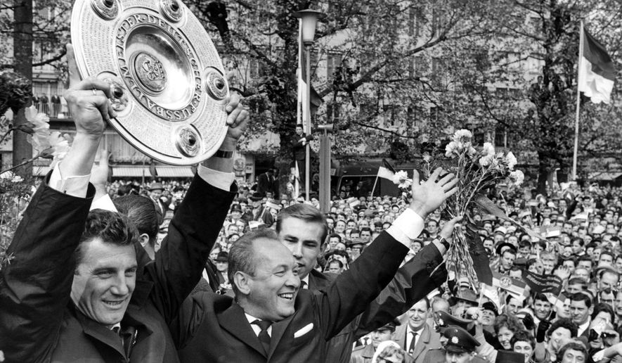 """FILE - In this May 13, 1962 file photo 1. FC Cologne soccer captain Hans Schaefer celebrates with the Champions trophy next to coach Zlatko 'Tschik' Cajkovski in Cologne, West Germany.Hans Schaefer, a member of Germany's 1954 World Cup winning-squad, has died at the age of 90.His long-time team Cologne said Schaefer died Tuesday Nov. 7, 2017, calling his death an """"indescribable loss"""" for the club and the city.  (dpa/dpa via AP)"""