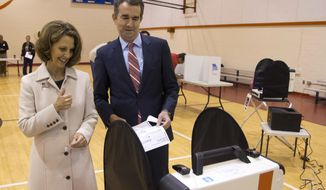 Democratic gubernatorial candidate Lt. Gov. Ralph Northam, and his wife, Pam, approach the vote tally machine as the vote in Norfolk, Va., Tuesday, Nov. 7, 2017. Northam faces Republican Ed Gillespie in today's election. (AP Photo/Steve Helber)
