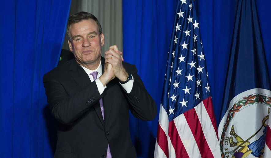 Senate Intelligence Committee Vice Chairman Sen. Mark Warner, D-Va., walks onstage to address the Ralph Northam For Governor election night party at George Mason University in Fairfax, Va., Tuesday, Nov. 7, 2017. (AP Photo/Cliff Owen)